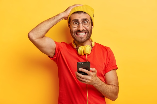 Embarrassed hipster clenches teeth, looks nervously, cannot download necessary application on smart phone, has headphones around neck, dressed casually