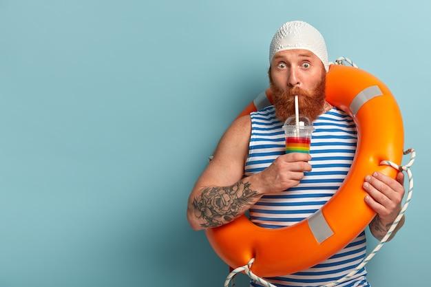 Смущенный отдыхающий пьет холодный летний коктейль, проводит свободное время на пляже, носит матросскую футболку swimcap