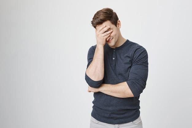 Смущенный человек facepalm и улыбается