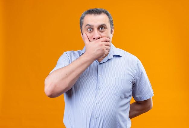 Смущенный мужчина средних лет в синей рубашке в вертикальную полоску прикрывает рот рукой