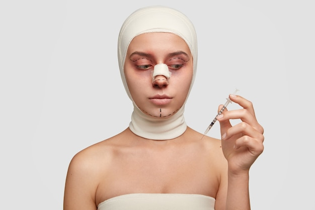 Embarrassed model after rhinoplasty or nose reshaping, going to have rhytidectomy, holds syringe vaccine of painkiller, wants to have perfect soft healthy skin, isolated over white background