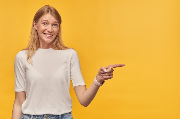 Embarrassed pretty woman with freckles in white tshirt standing and pointing away to the side at empty space by finger on yellow