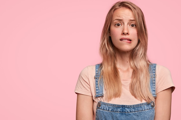 Embarrassed puzzled lovely woman bites lips, has miserable facial expression, dressed in fashionable denim overalls