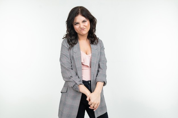 Embarrassed reserved girl in a gray jacket on a white background with copy space