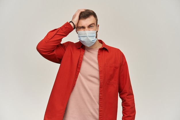 Embarrassed sad young bearded man in red shirt and virus protective mask on face against coronavirus keeps hand on head and having a headache over white wall