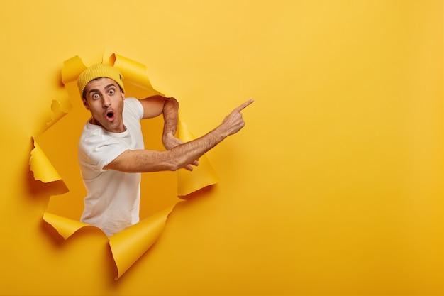 Un uomo europeo imbarazzato e scioccato punta il dito indice per copiare spazio, consiglia il servizio, mostra il nuovo prodotto, tiene la bocca ben aperta dalla sorpresa
