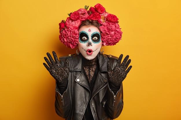 Donna imbarazzata e scioccata vestita con abiti tradizionali o abiti per onorare i morti in messico, ha la bocca spalancata, il trucco del cranio, alza i palmi per lo stupore
