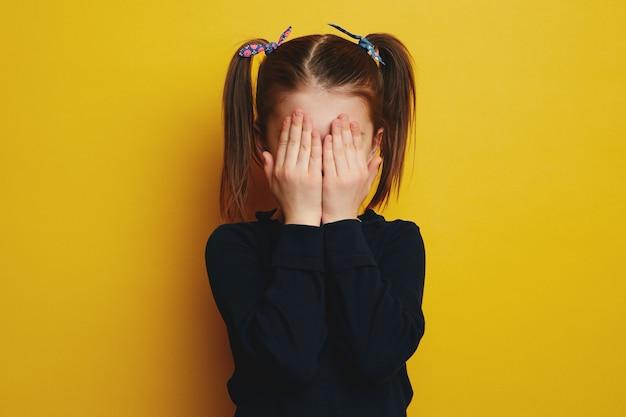 Смущенная застенчивая милая девушка с хвостиками, закрывающими лицо обеими руками