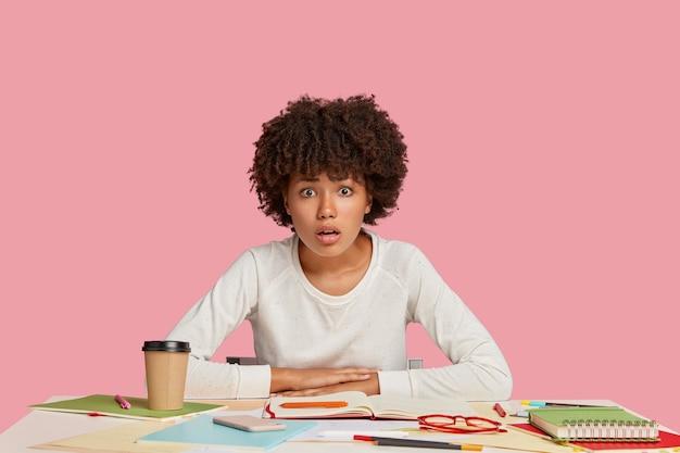 ピンクの壁に向かって机でポーズをとる恥ずかしい学生の女の子