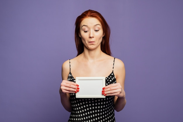 An embarrassed and surprised pretty woman holds an empty blank in her hands and looks at it. template for your advertisement and text. mock up for design
