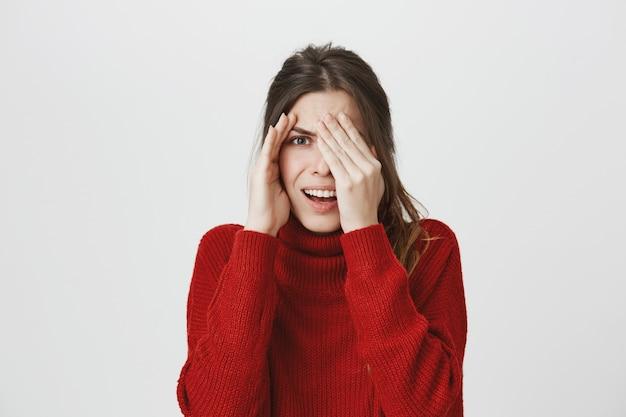 Embarrassed woman peeking at something disgusting