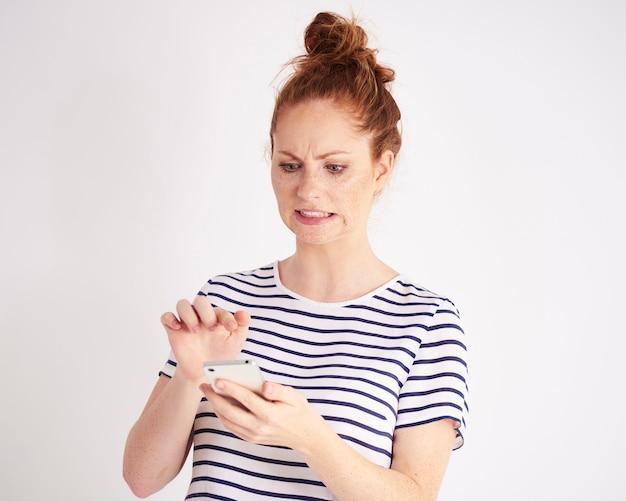 Смущенная женщина, использующая снимок мобильного телефона