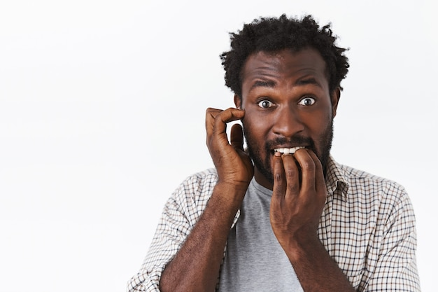 Embarrassed and worried bearded african-american guy feel panic, biting nails and scratch ear, stare anxious