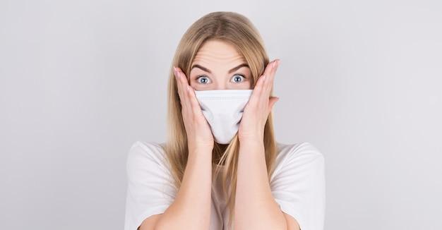 격리 된 흰색 배경 위에 서 의료 마스크를 쓰고 당황 젊은 백인 여자