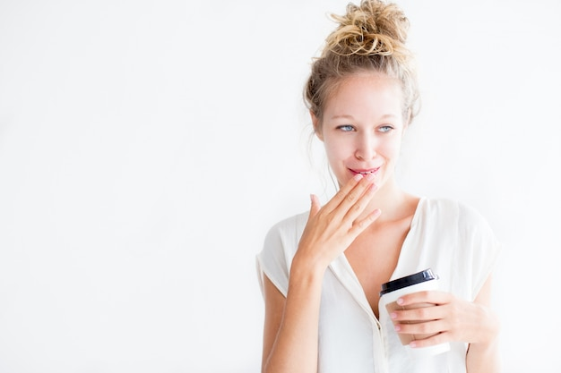 Embarrassed young lovely woman holding drink
