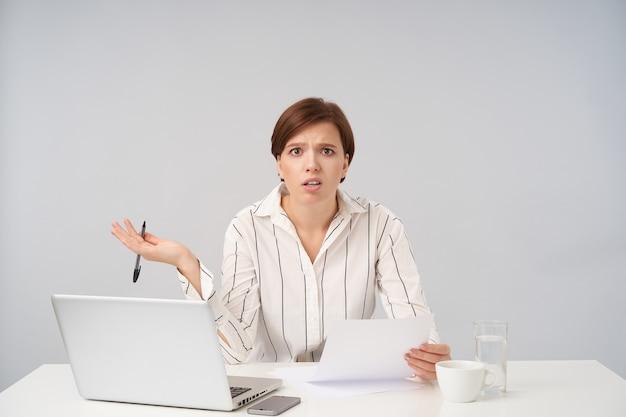 Imbarazzata giovane donna bruna dai capelli corti con trucco naturale non riesce a capire con documenti e guarda confusamente, sopracciglia accigliate con palmo sollevato su bianco