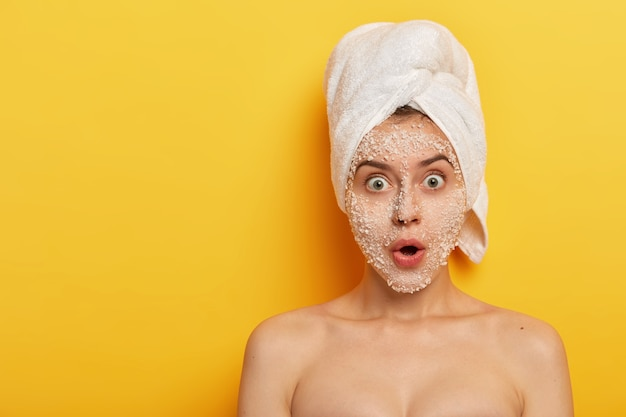 Embarrassed young woman stands shirtless, applies peeling facial mask for removing dark dotes on face, stares at camera wears white soft towel on head isolated on yellow