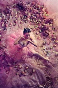 Imbarazzo. vista dall'alto di bella giovane donna in tutu di balletto rosa circondato da fiori. atmosfera primaverile e tenerezza nella luce del corallo. concetto di primavera, fioritura e risveglio della natura.