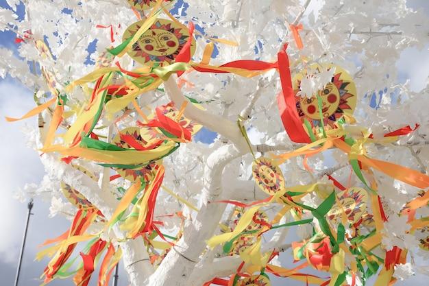 Эмблема солнца с разноцветными лентами на ветвях белого дерева, символ карнавала на белом дереве в парке, картина солнца, масленица в парке, изображения солнца с лентами на масленице, масленица