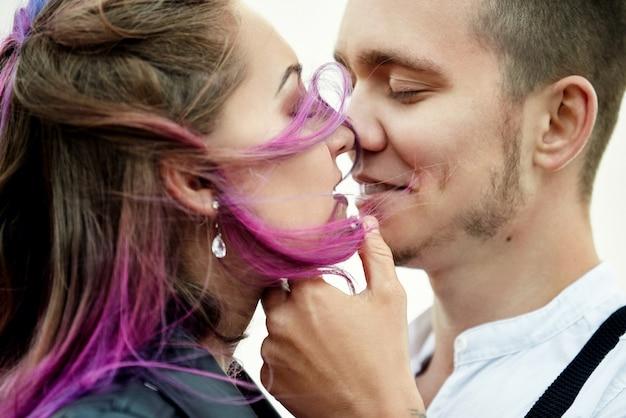 Обнимите и поцелуйте влюбленную пару весенним утром на природе. день святого валентина, близкие отношения между мужчиной и женщиной. мужчина целует девушку с яркими волосами, креативная раскраска