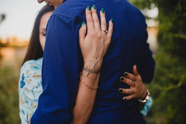 The embrace of a couple in love. girl's hand on her friend's back close up