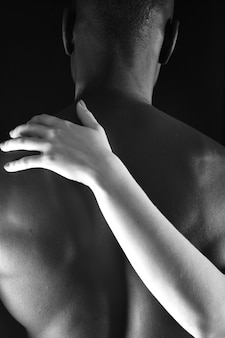The embrace of an interracial couple on black background