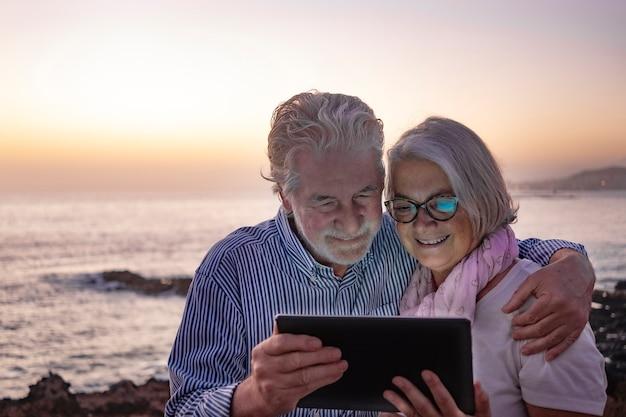 백그라운드에 물 위에 수평선과 해변에 앉아 황혼에 디지털 태블릿을보고 매력적인 수석 부부 백발을 포용. 함께 행복한 은퇴 개념
