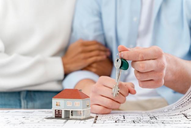 Coppie sfocate abbracciate che tengono le chiavi della loro nuova casa