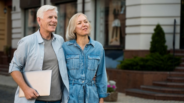 Embraced older couple outdoors in the city with tablet