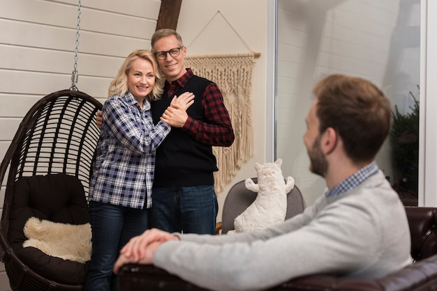 Embraced parents smiling at son on sofa