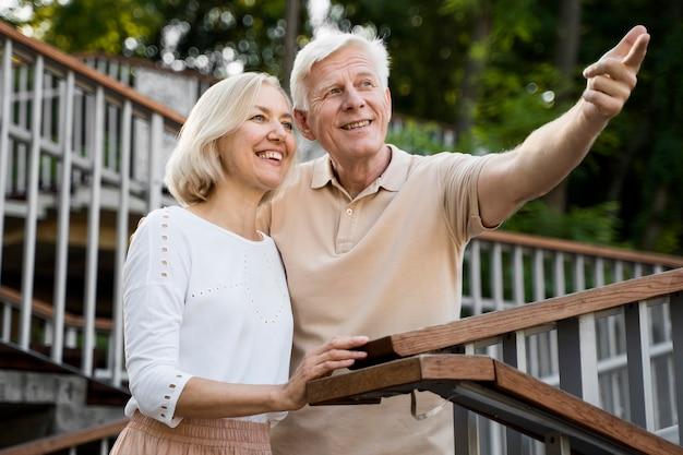 屋外の眺めを楽しみながら年配のカップルを採用