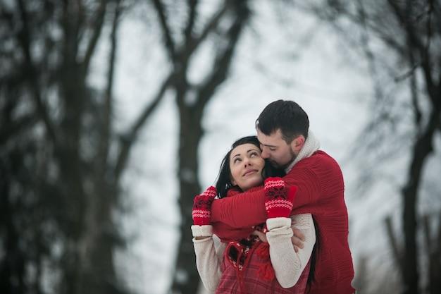 Охватывая пару в зимнем лесу