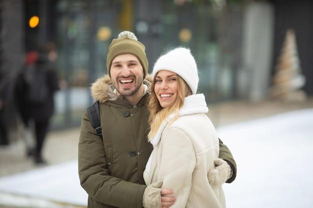 겨울 공원에서 미소를 가진 카메라를보고 몇 포용.