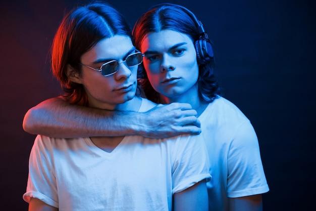 Обнимая друг друга. портрет братьев-близнецов. студия снята в темной студии с неоновым светом