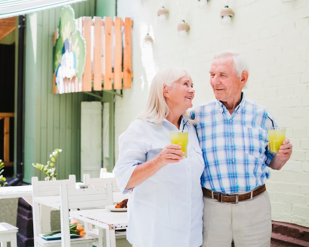 Embracing elderly couple drinking juice in cafe