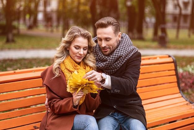 Обнимая счастливая пара, сидящая нежно романтично и обнимающаяся на скамейке в парке в пальто и шарфах