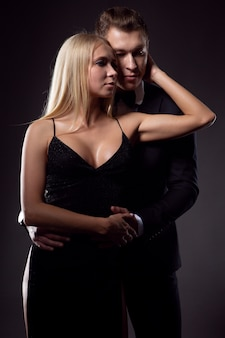Embracing lovers man and woman in elegant evening dresses
