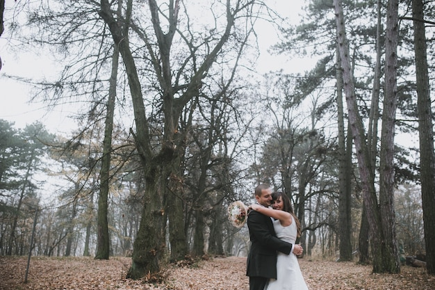 Embracing newlyweds in leafless forest