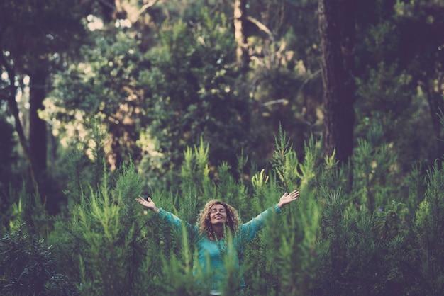 完全な幸福と喜びで森の木々の真ん中で幸せな美しい女性とアウトドアと愛の自然の概念を受け入れる