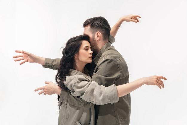 抱きしめる。白いスタジオの壁に分離されたトレンディなファッショナブルなカップル。