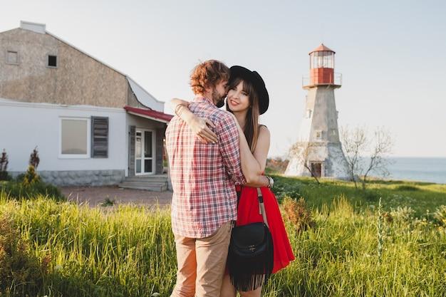 Обнимая молодую стильную влюбленную пару в сельской местности, в богемном стиле инди-хипстеров, каникулах на выходных, летнем наряде, красном платье, зеленой траве, держась за руки