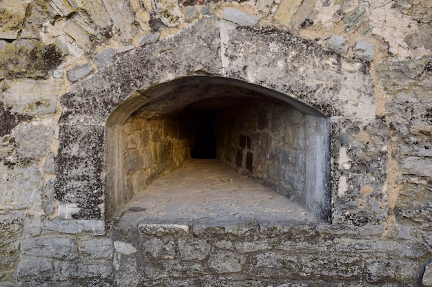 An embrasure for shooting in the thick wall of an old fortress or castle. covered with rough stone