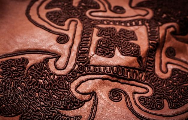 Вышитый орнамент на коричневой фактуре кожи