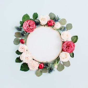 淡いパステルブルーで分離されたベージュのバラの花のつぼみの刺繡フレーム