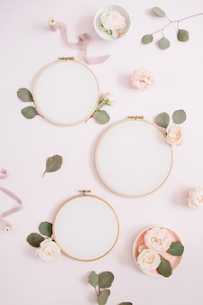 Embroidery frames with beige rose flower buds and eucalyptus on pale pastel pink background. flat lay, top view