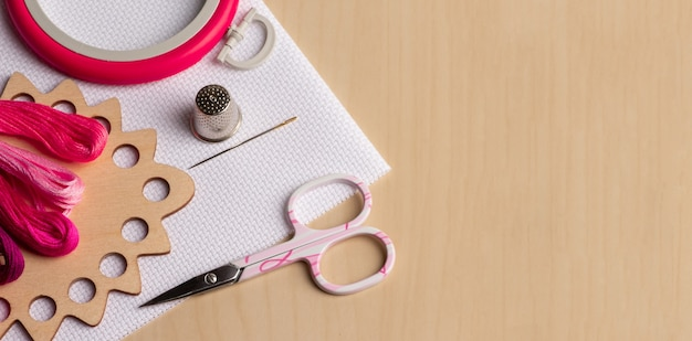 Набор для вышивания на деревянном столе. канва, обруч, розовая нить, наперсток, игла, ножницы. копировать пространство вид сверху