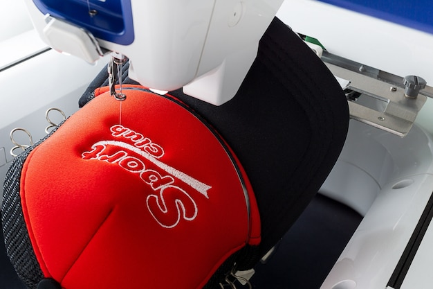 Embroidery machine and embroidered sport cap close up image