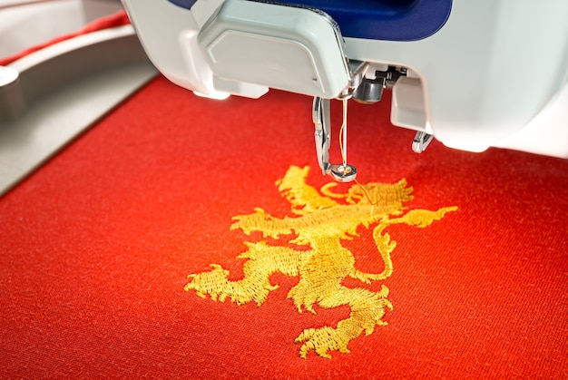 Embroidery machine and gold lion design on red cotton fabric shirt