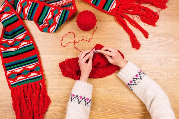 Embroidery maker workplace. woman female embroidering red striped national ukrainian towel  and balls of thread