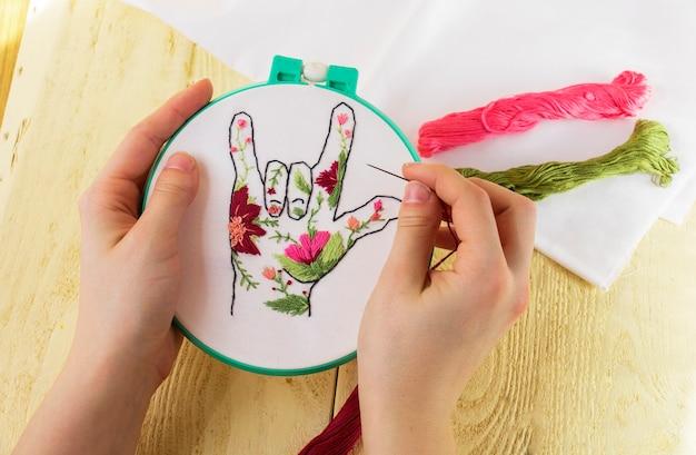 女の子の手のキャンバスに刺繡。上からの眺め。刺繡、一種の針仕事、創造性、芸術として。花の指の刺繡